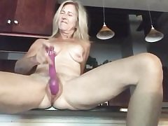 Nude ash-blonde stretches out her gams rubbing pussy with a large fuck stick
